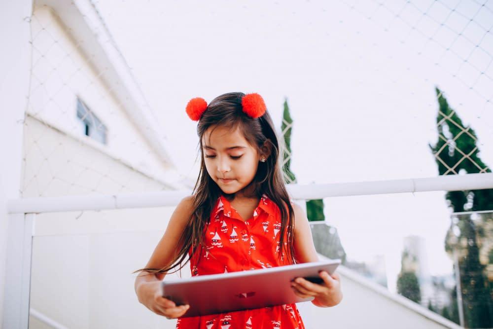 Meisje met rood jurkje gebruikt een tablet