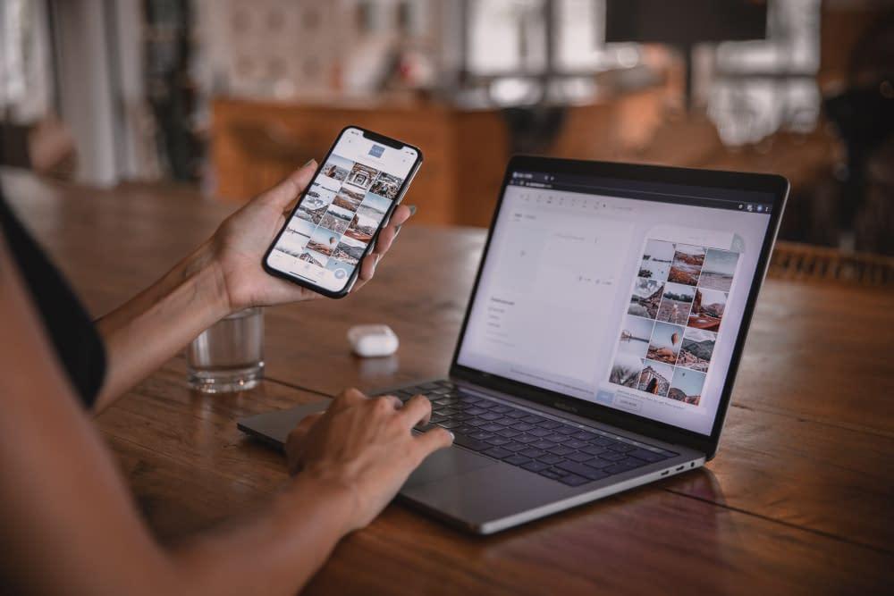 Vrouw gebruikt een laptop en telefoon daarop dezelfde content
