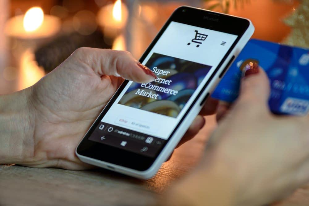 Twee handen houden een telefoon en een creditcard vast