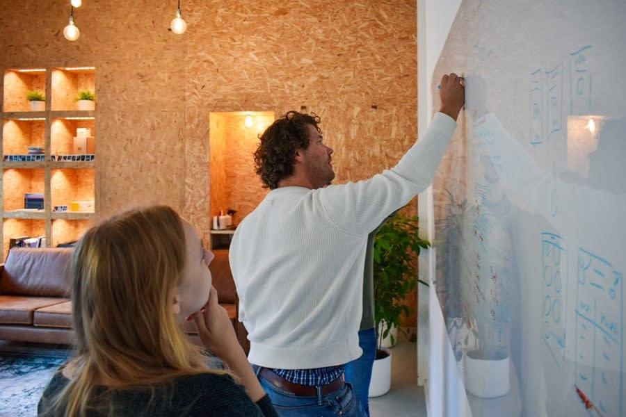 Foto van kristine, robert en reinoud op het kantoor van Brthrs. Terwijl ze tekenen op een whiteboard